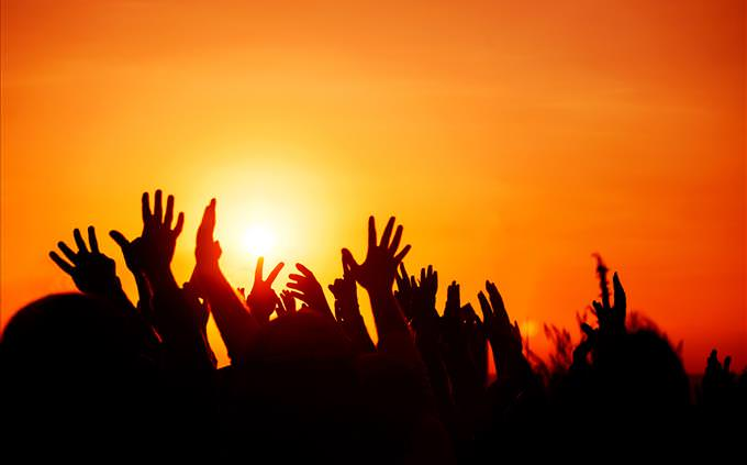 hands raised in the air at dusk