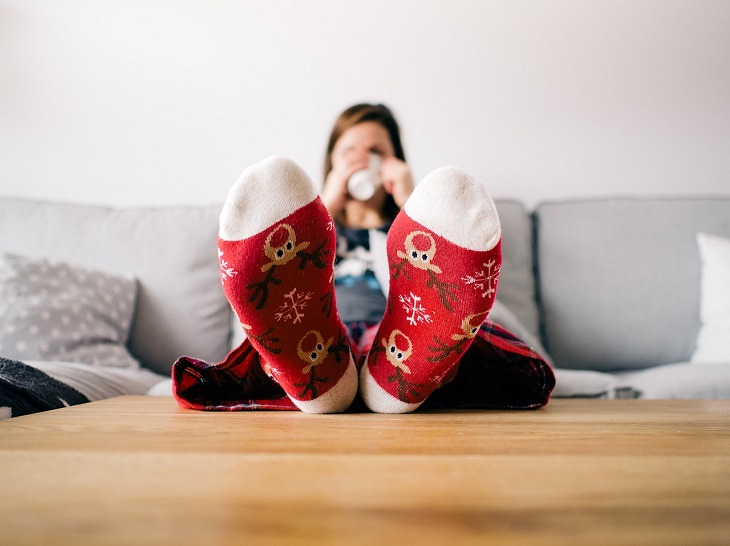 woman drinking coffee on the couch with colorful socks