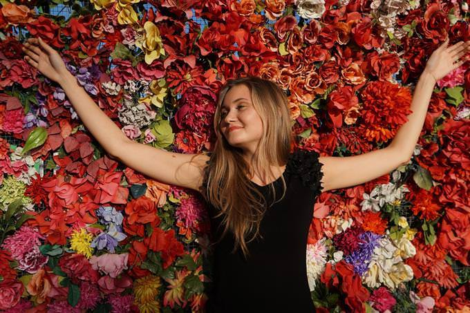 A woman with her arms spread sideways in front of a wall of flowers