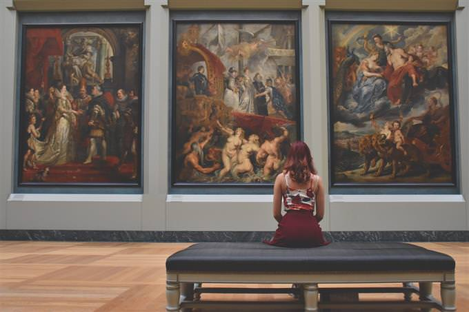 A woman looking at paintings in a museum