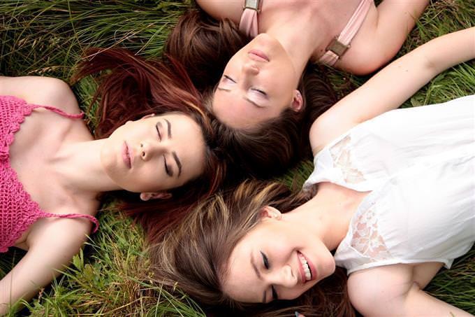 Women lying on grass head to head
