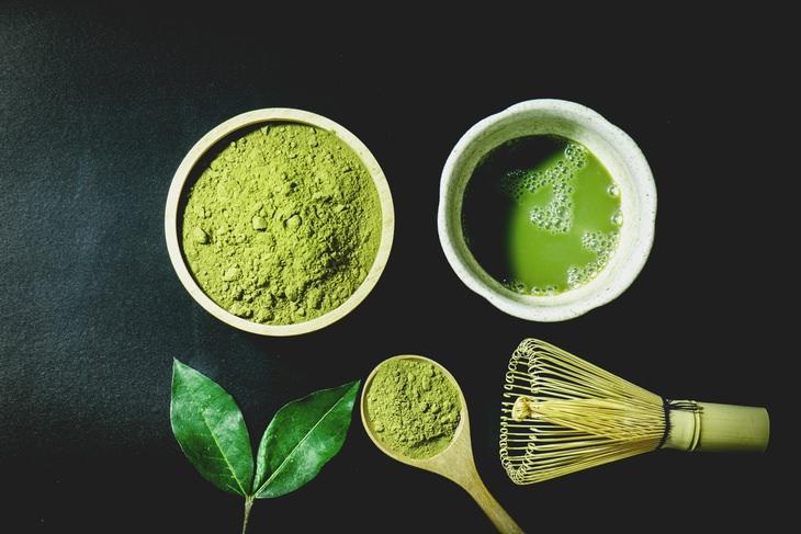 matcha powder, tea leaves, a cup of matcha, a matcha whisk and a spoonful of matcha