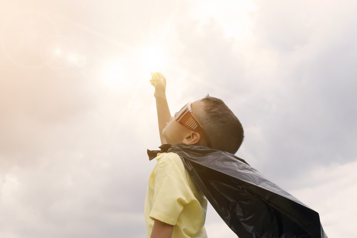 boy in glasses and a cape reaching for the Sun