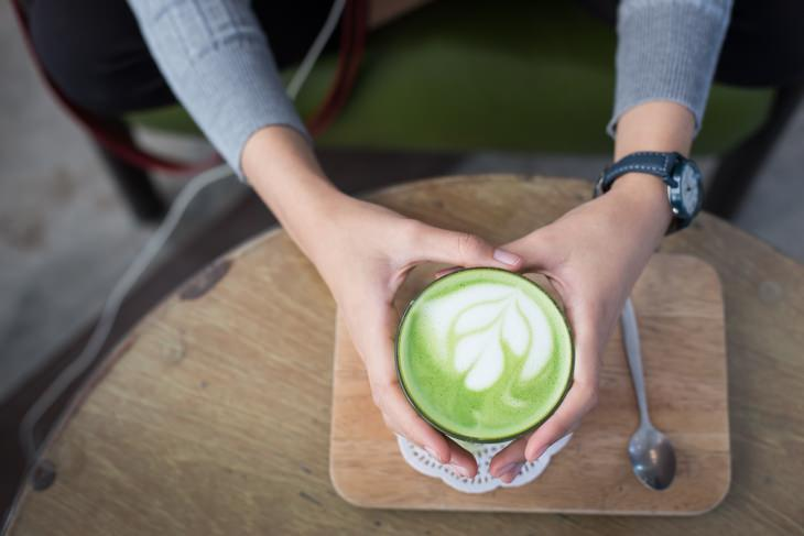 a woman holding a cup of matcha latte