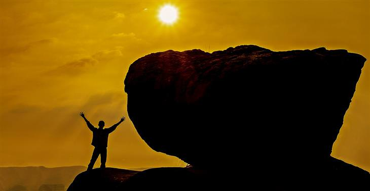 habits: silhouette of a man next to a boulder