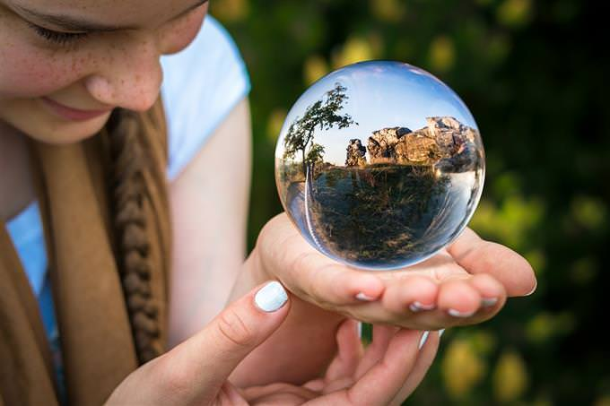 How your life flows: A girl looking at a landscape that appears inside a crystal ball