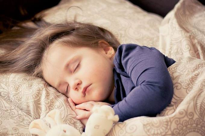 A girl sleeping with a teddy bear