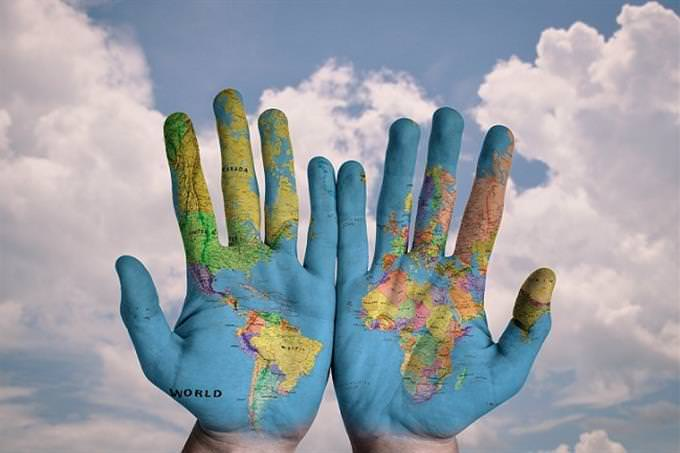A pair of hands on which a map of the world is drawn