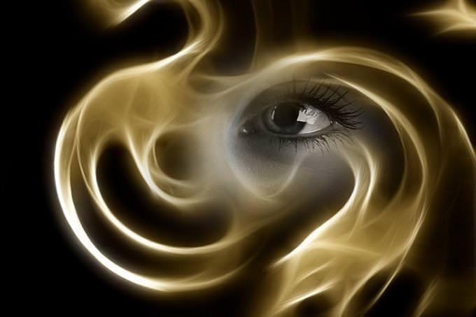 An eye behind curling smoke
