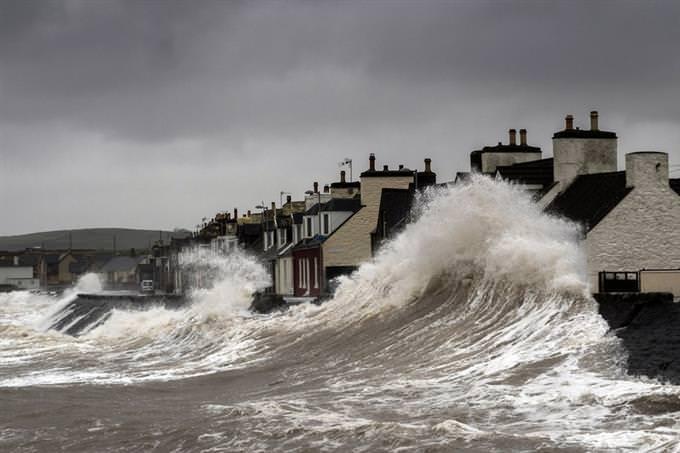 Sea waves crashing on homes