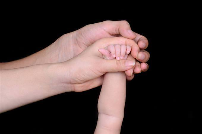 A woman's hand holding the hand of a baby