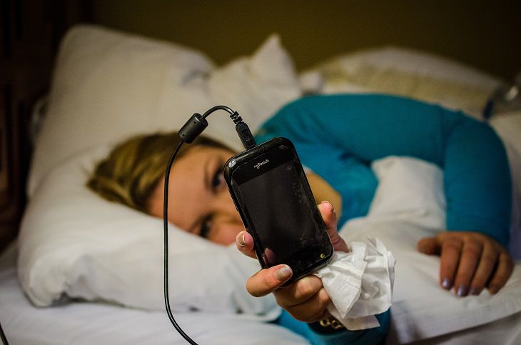 woman in bed looking at her charging cellphone