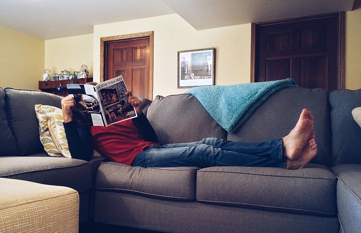 man laying on a couch reading a magazine