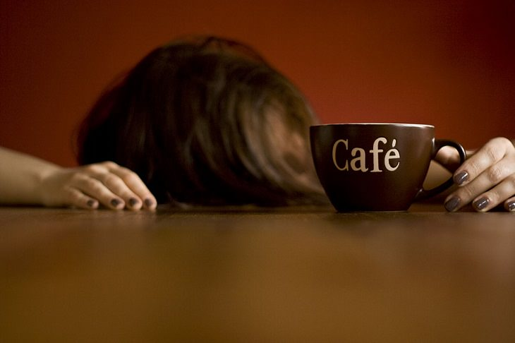 woman with her head down on the table holding a cup of coffee