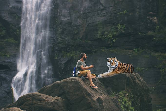 A man sitting beside a tiger in front of a waterfall
