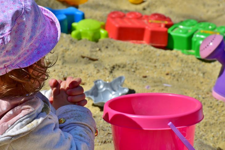 a child playing with a plastic bucket on the beach