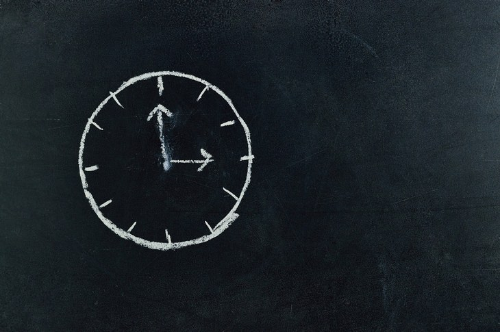 a clock drawn on a chalkboard with white chalk