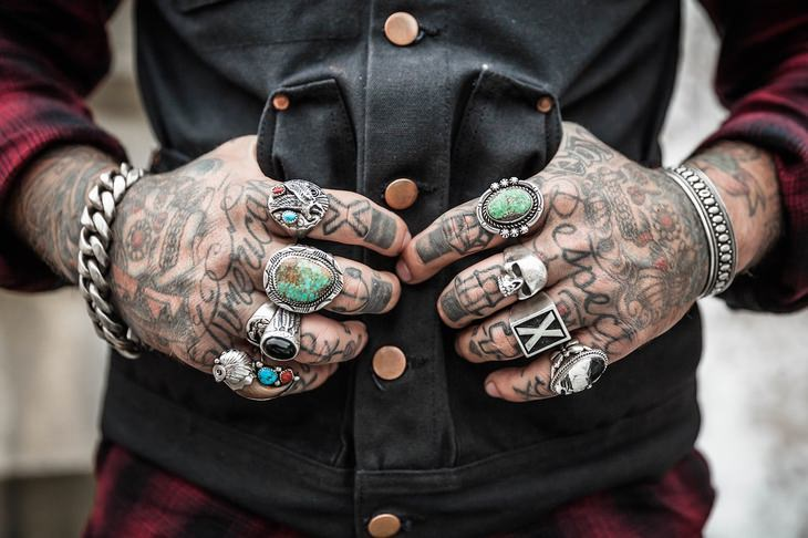 a man's tattoed hands with rings and bracelets