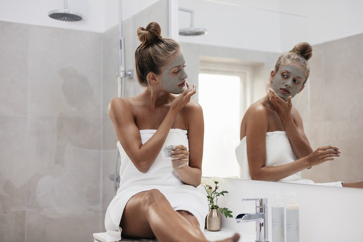 a woman in a bathroom wearing a face mask