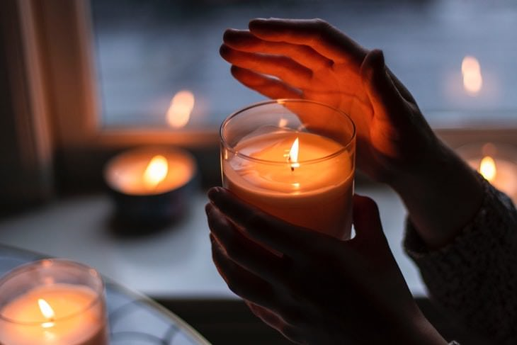 Dog Health Hazards in Home and Garden person holding a candle