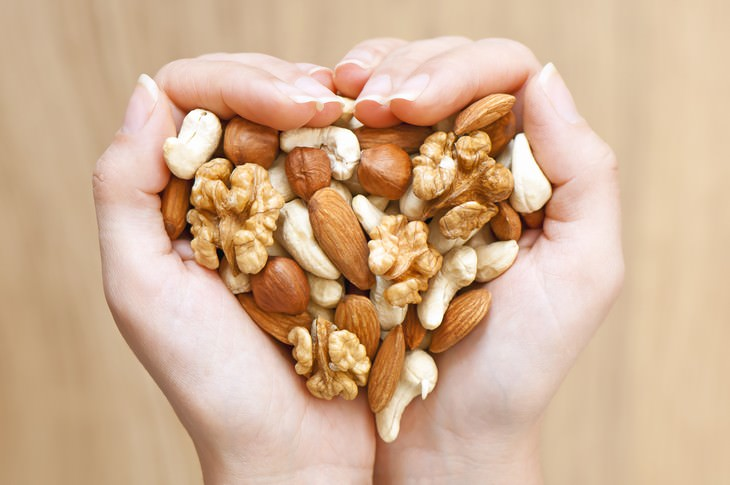 The 10 Healthiest Nuts woman holding different nuts in her hands