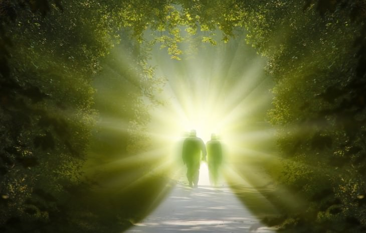 couple in heavenly light surrounded by forest