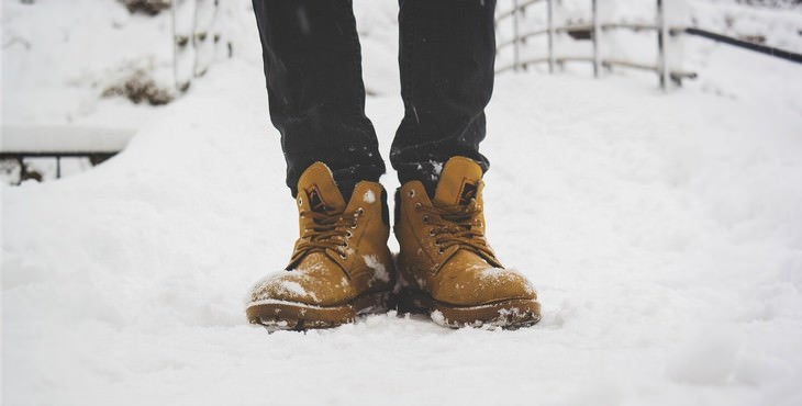 winter lawn care tips person wearing winter boots in the snow