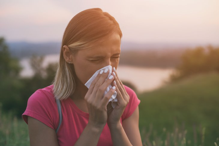 Myths about the Cold and Flu woman blowing nose with tissue