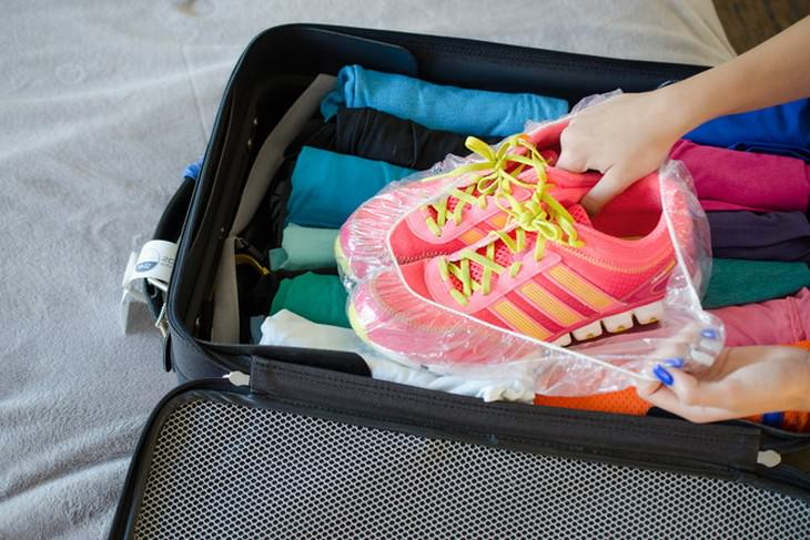 packing and hotel tricks shower cap on sneakers in suitcase