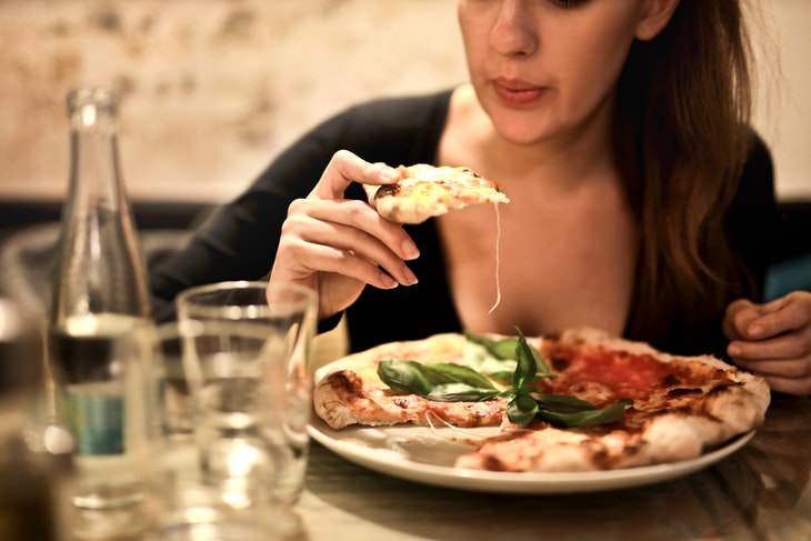 Heavy Evening Meals Affect Women's Heart Health woman eating pizza for dinner
