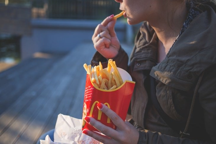 most and least addictive foods woman eating french fries