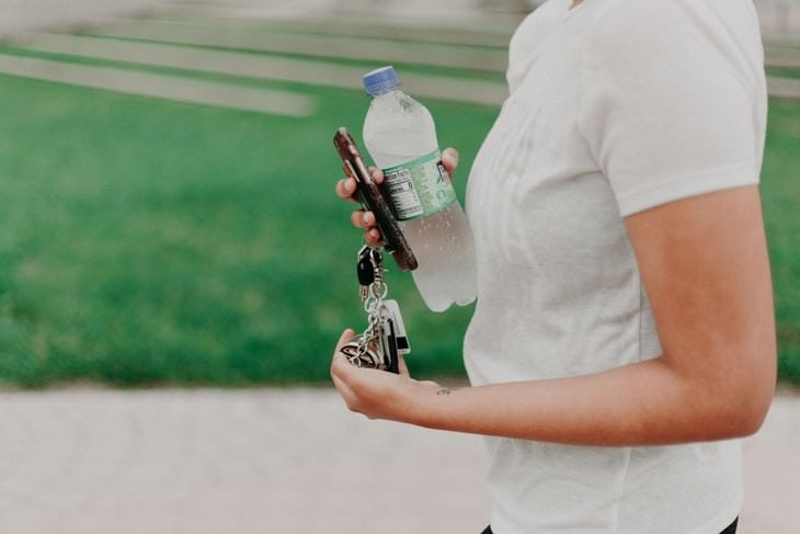 health myths of the 2010's woman carrying a bottle of water and keys