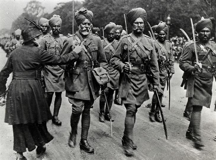historical photos A French woman attaching flowers to uniforms of British-Indian army soldiers who assisted the fighting in France