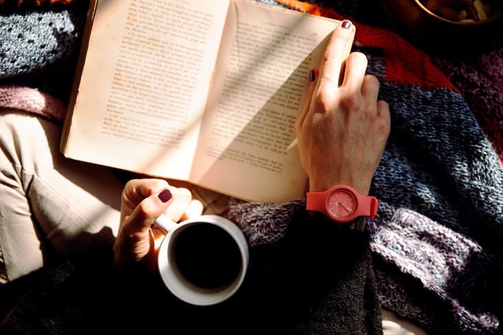language learning woman reading a book while drinking coffee