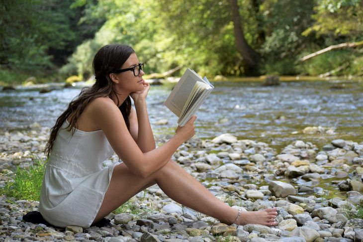 signs you are a better person woman reading on the river bank