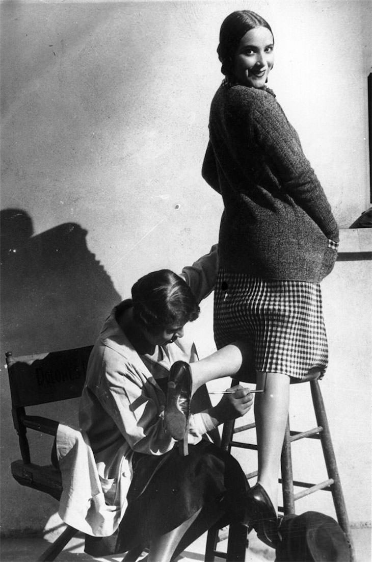 Past Beauty Practices That Seem Strange Today, A woman aaving a seam painted onto her leg, tom it appear that she is wearing stockings, 1926