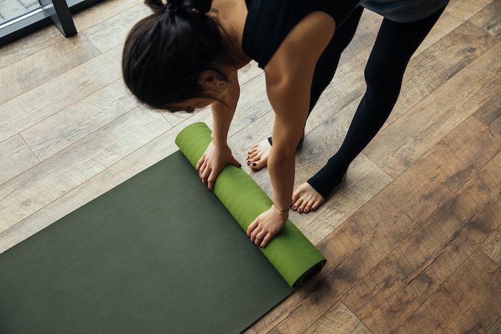 Restorative Yoga: Health Benefits and Simple Poses, woman rolling yoga mat