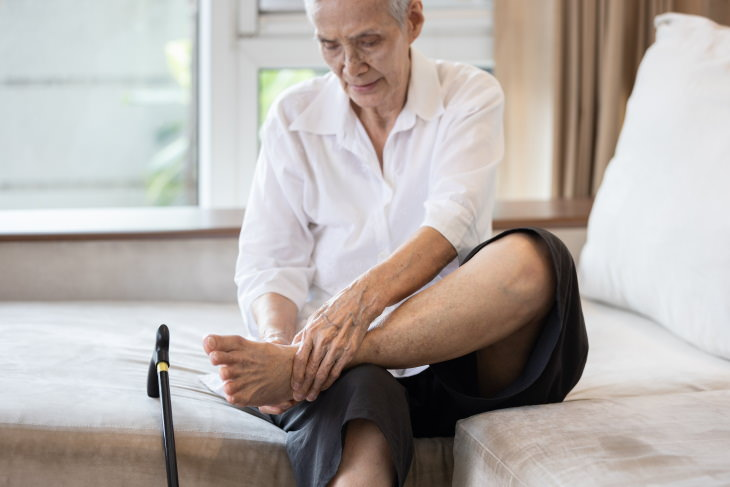 Cold Feet Causes and Remedies woman sitting and hold her foot
