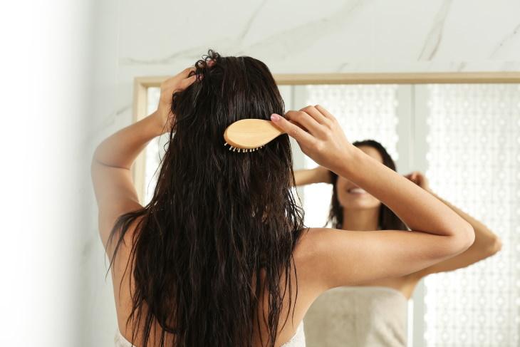 Hair Care Mistakes woman Brushing wet hair