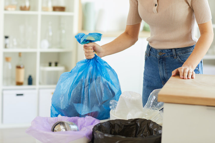 Take Out the Trash Easily with These Hacks, woman taking out trash bag out of can