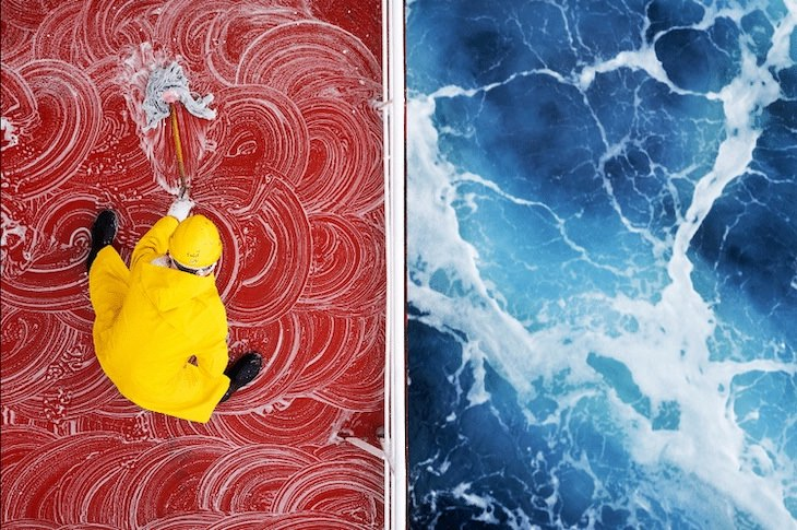 12 Unforgettable Photos of Asia by Zay Yar Lin, While cruising at sea, a sailor swabs the deck of a ship's red deck