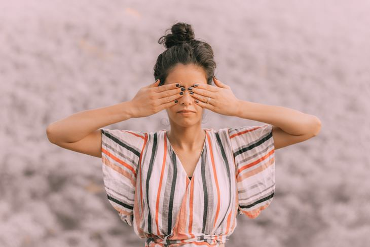 Eye Yoga woman covering her eyes with her hands