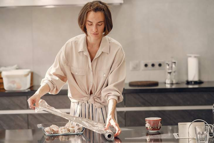 Aluminum Foil - Should You Use the Sticky or the Dull Side, woman using aluminum foil in kitchen
