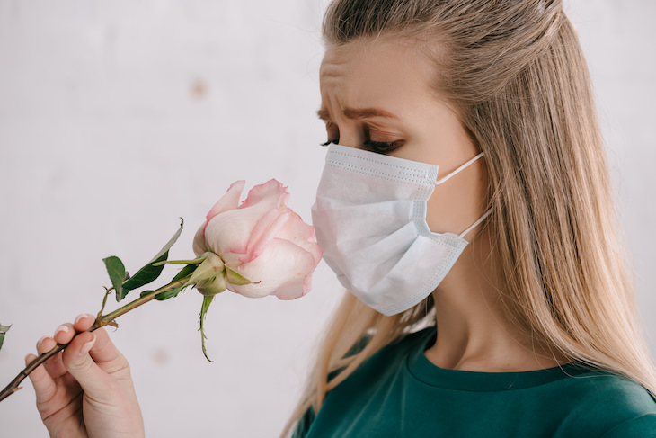 Subtle Sign You Might've Already Had Covid-19, woman with face mask smelling a flower