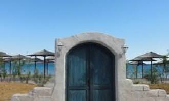 door built into a wall on the beach