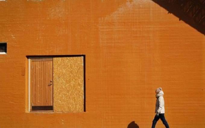Man walking near orange wall