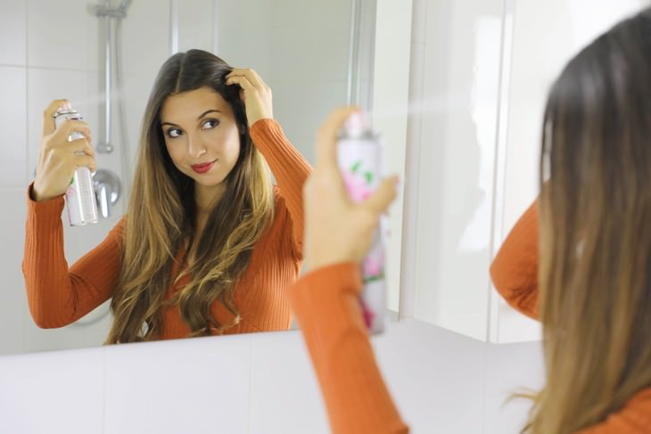 Tips to Help You Get Rid of Greasy Hair woman applying dry shampoo