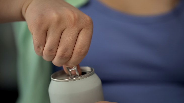 dangers of energy drinks woman opening a can