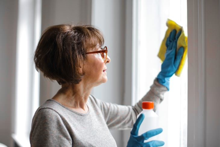 Spring Cleaning Health Benefits woman cleaning windowsill