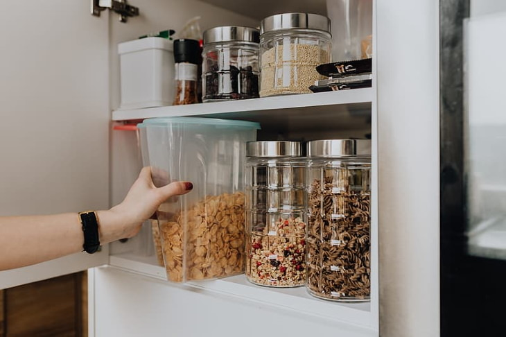 Spring Cleaning Health Benefits pulling out cornflakes out of the pantry